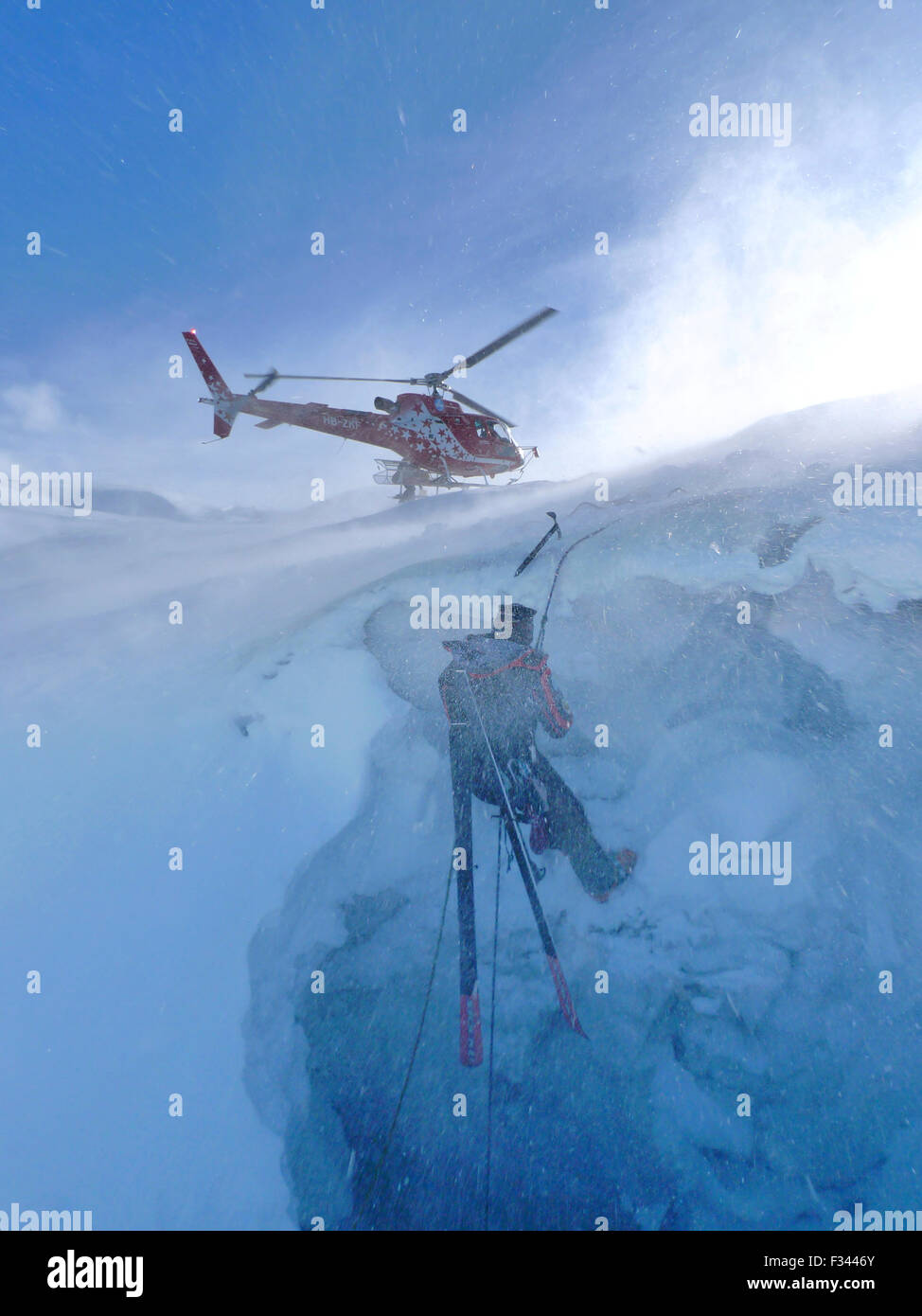 A mountain rescue technician is descending into a crevasse. When an off piste skier breaks through the snow and - Stock Image