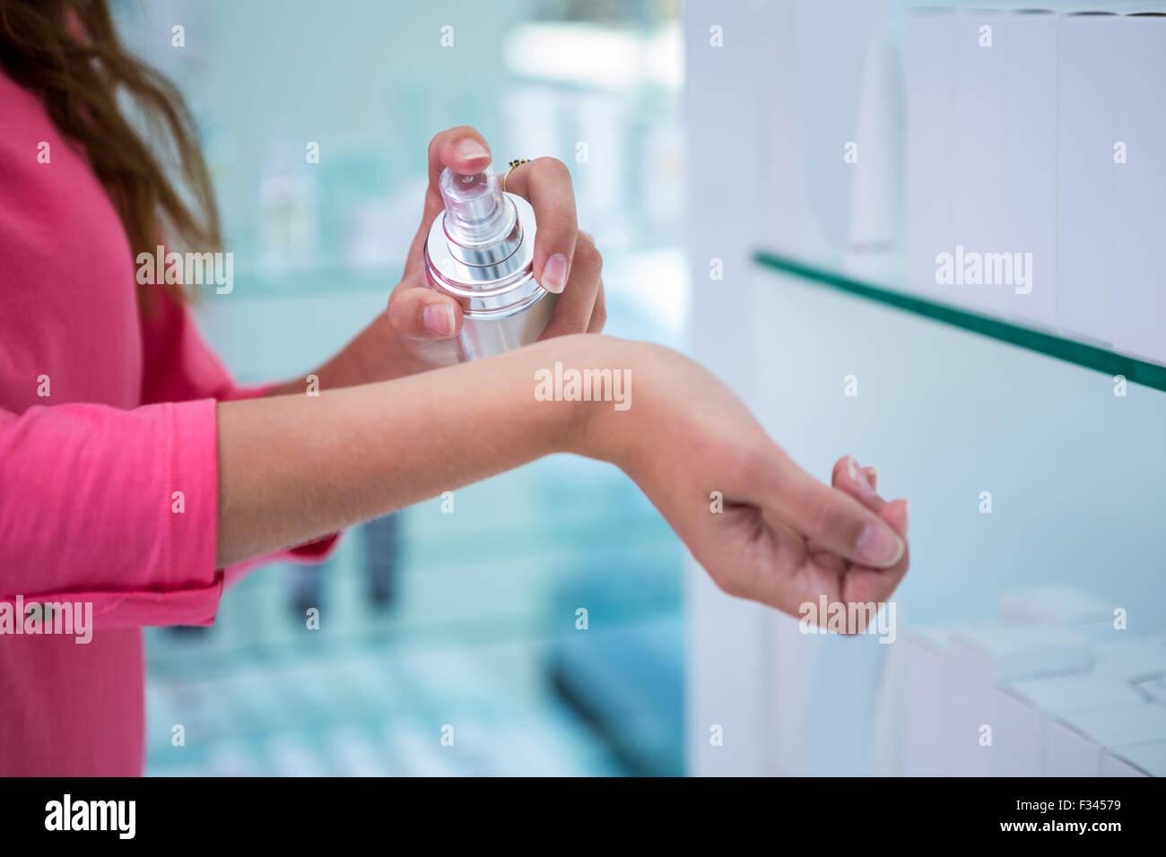 Woman spraying perfume on her wrist - Stock Image