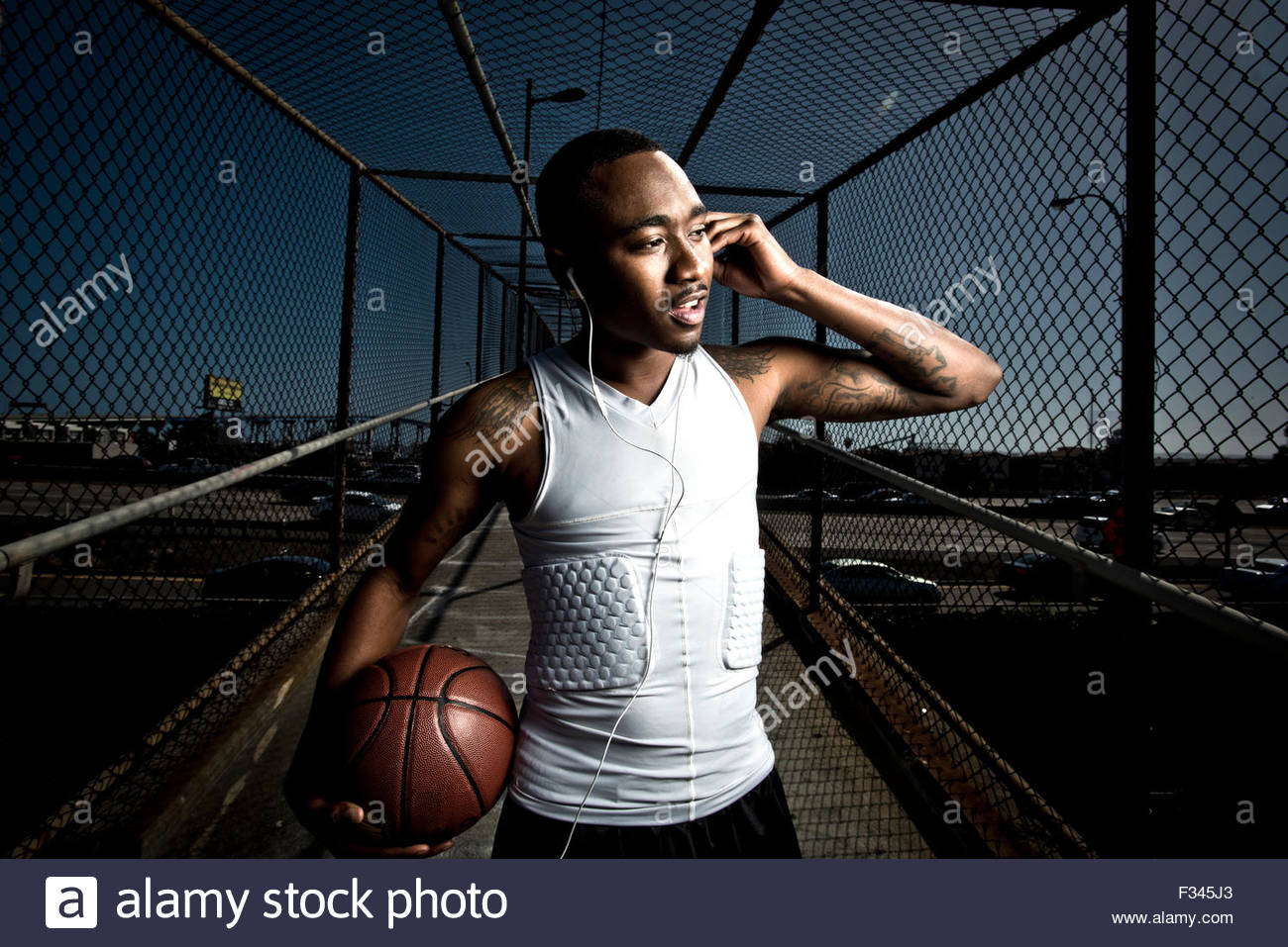A basketball player walks down a footbridge. - Stock Image