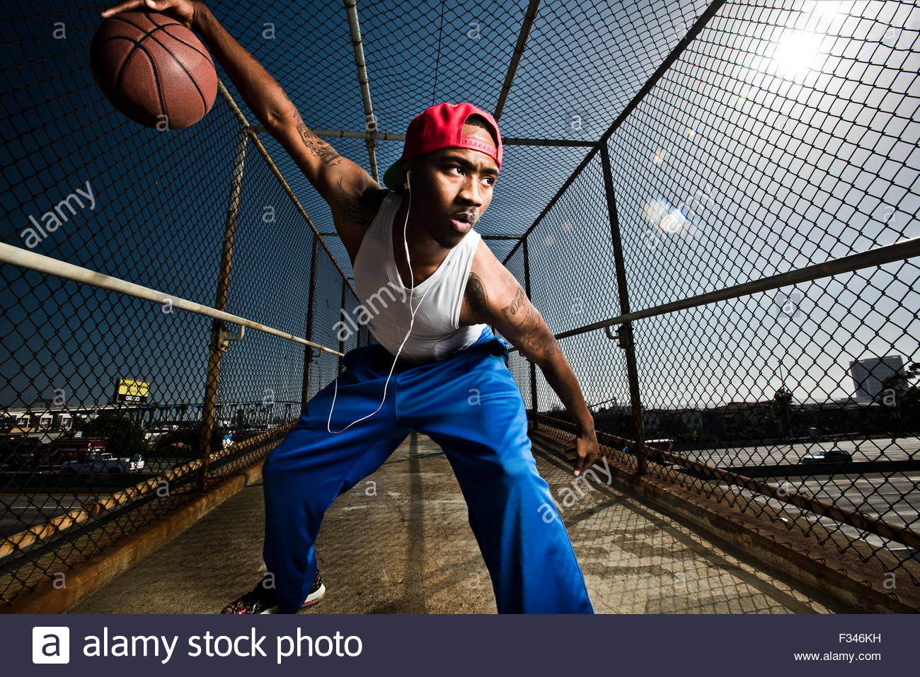 A basketball player dibbling a ball. - Stock Image
