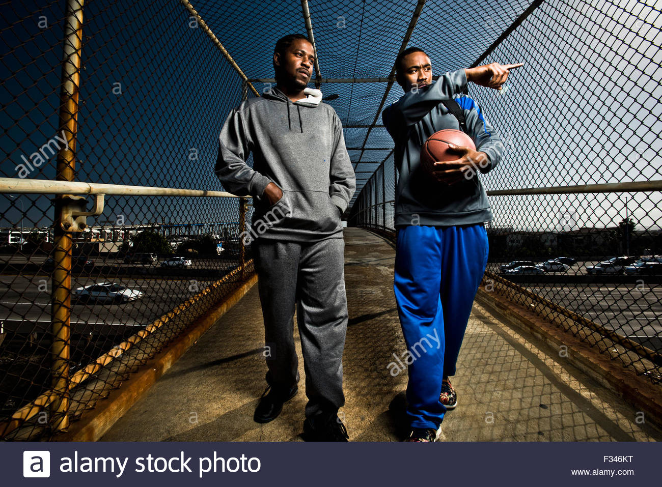 Two young men stroll with a basketball. - Stock Image