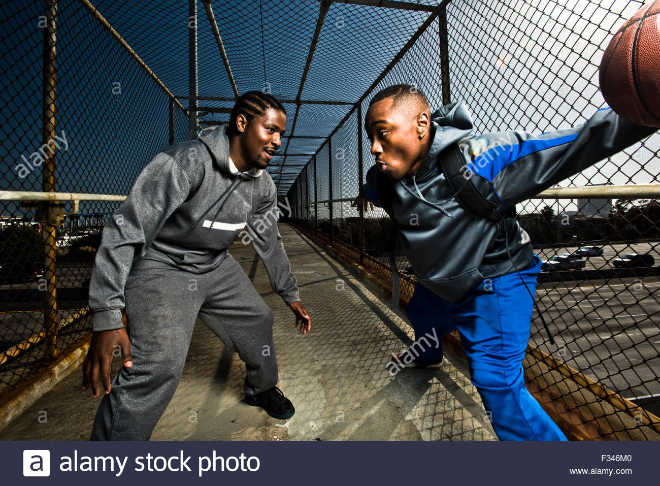 Two young guys walking down a foot bridge playing around with a basketball. - Stock Image