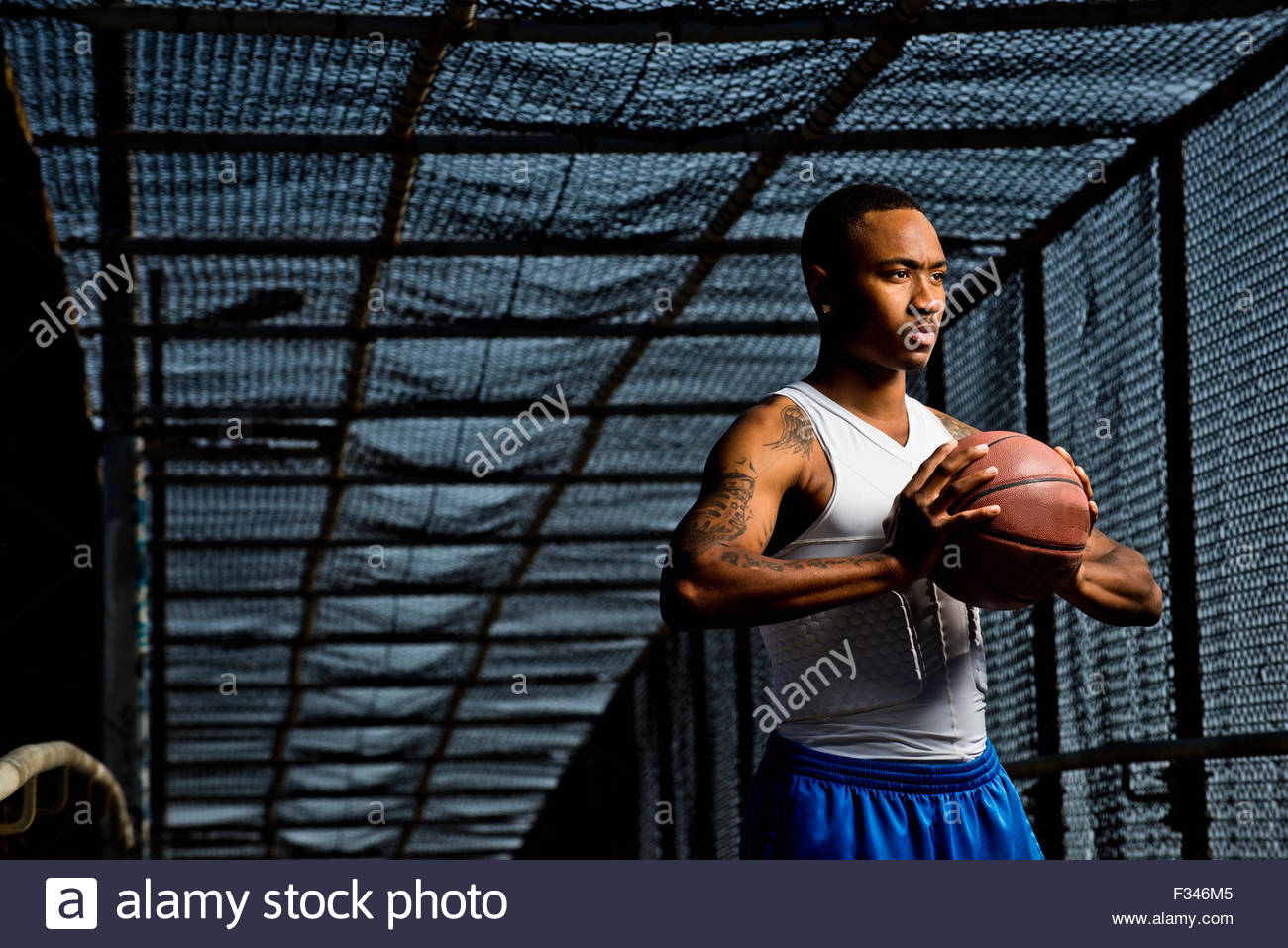 A young man poses with a basketball. - Stock Image