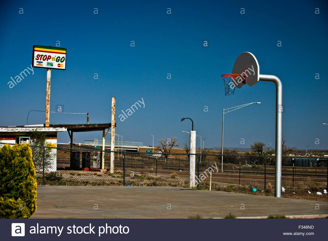 A deserted basketball court and gas station. - Stock Image