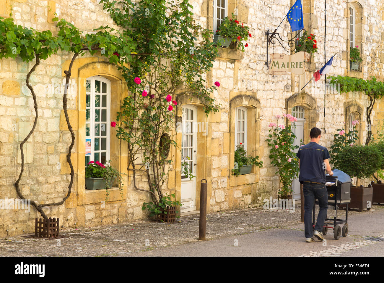 the Mairie in Monpazier with postman, Pays de Bergerac, Périgord, Dordogne, Aquitaine, France - Stock Image