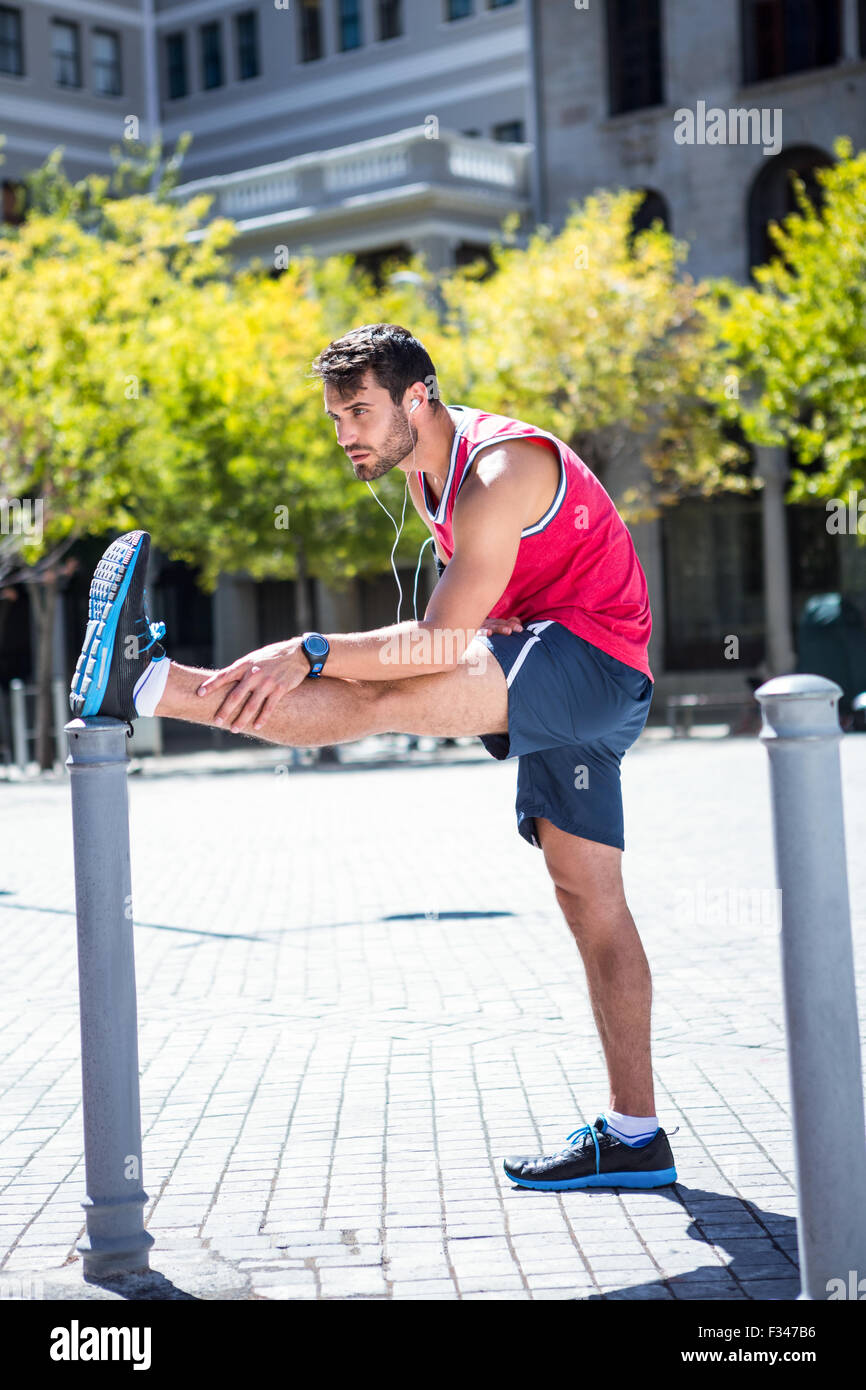 Handsome athlete doing leg stretching on a stake - Stock Image