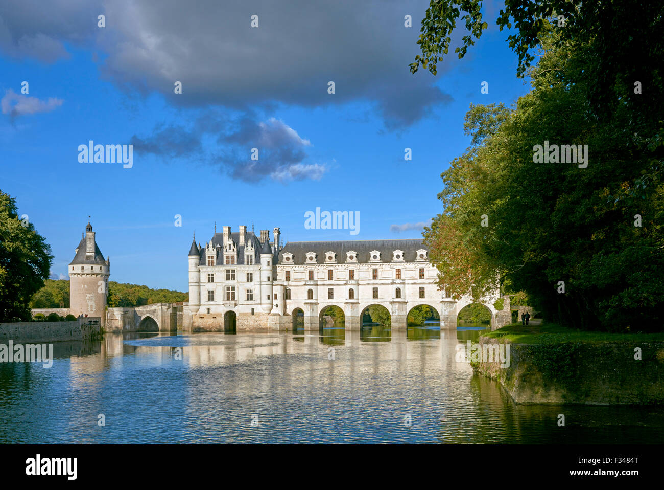 Château de Chenonceau and the River Cher, with couple walking on footpath. Chenonceaux, Indre-et-Loire, France. - Stock Image