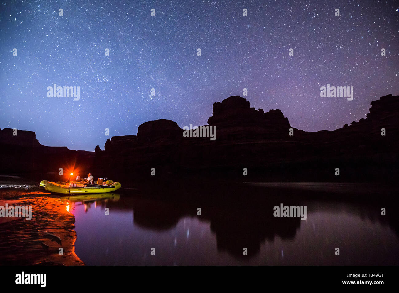 Glowing rafts on waters edge under a night sky. Stock Photo