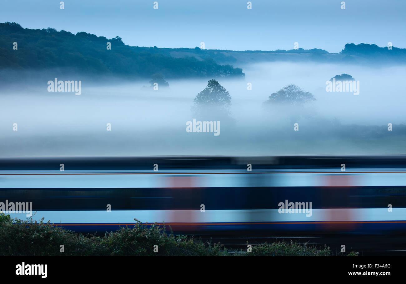 a train passing on a misty morning near Milborne Wick, Somerset, England, UK - Stock Image