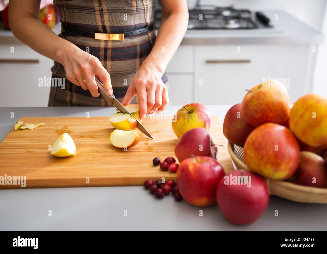 cutting; cut; woman; female; hands; apple; fruit; health; healthy; natural; board; anonymous; cutting board; applesauce; - Stock Image