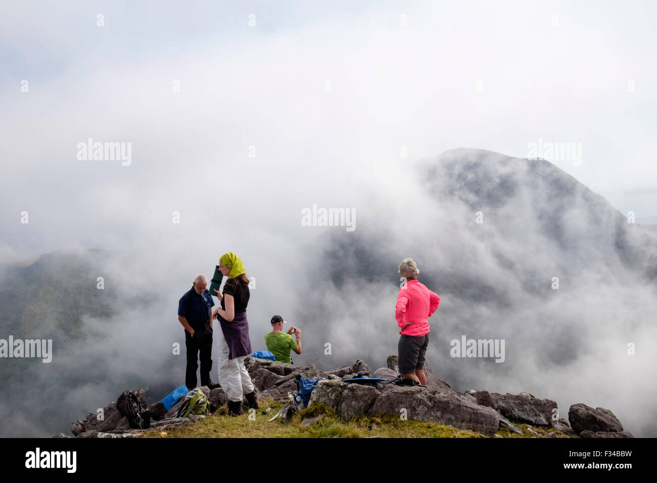 Hikers resting on Beenkeragh looking at view to Carrauntoohil through low cloud in MacGillycuddy Reeks County Kerry - Stock Image