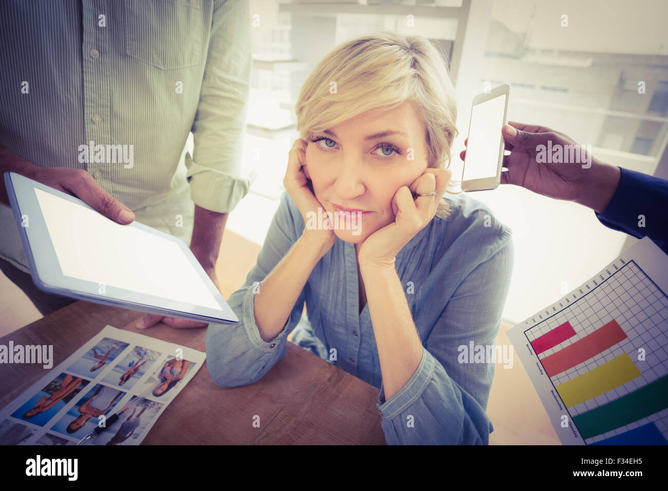 Overwrought businesswoman covering her ears - Stock Image