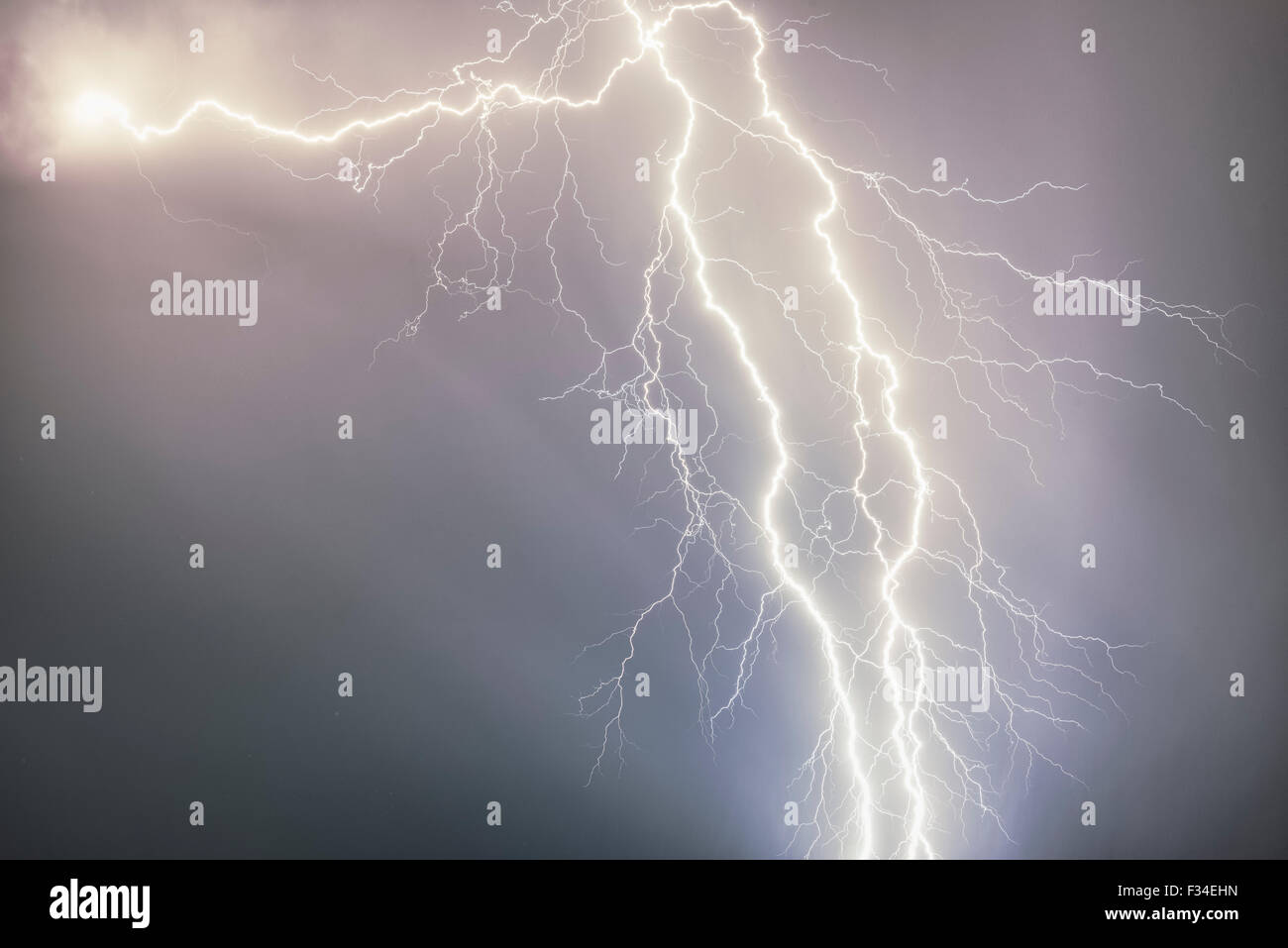 Forked lighting exploding from a cloud - Stock Image