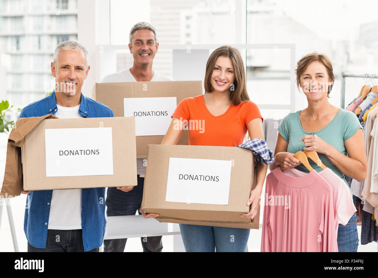 Smiling casual business people with donation boxes - Stock Image