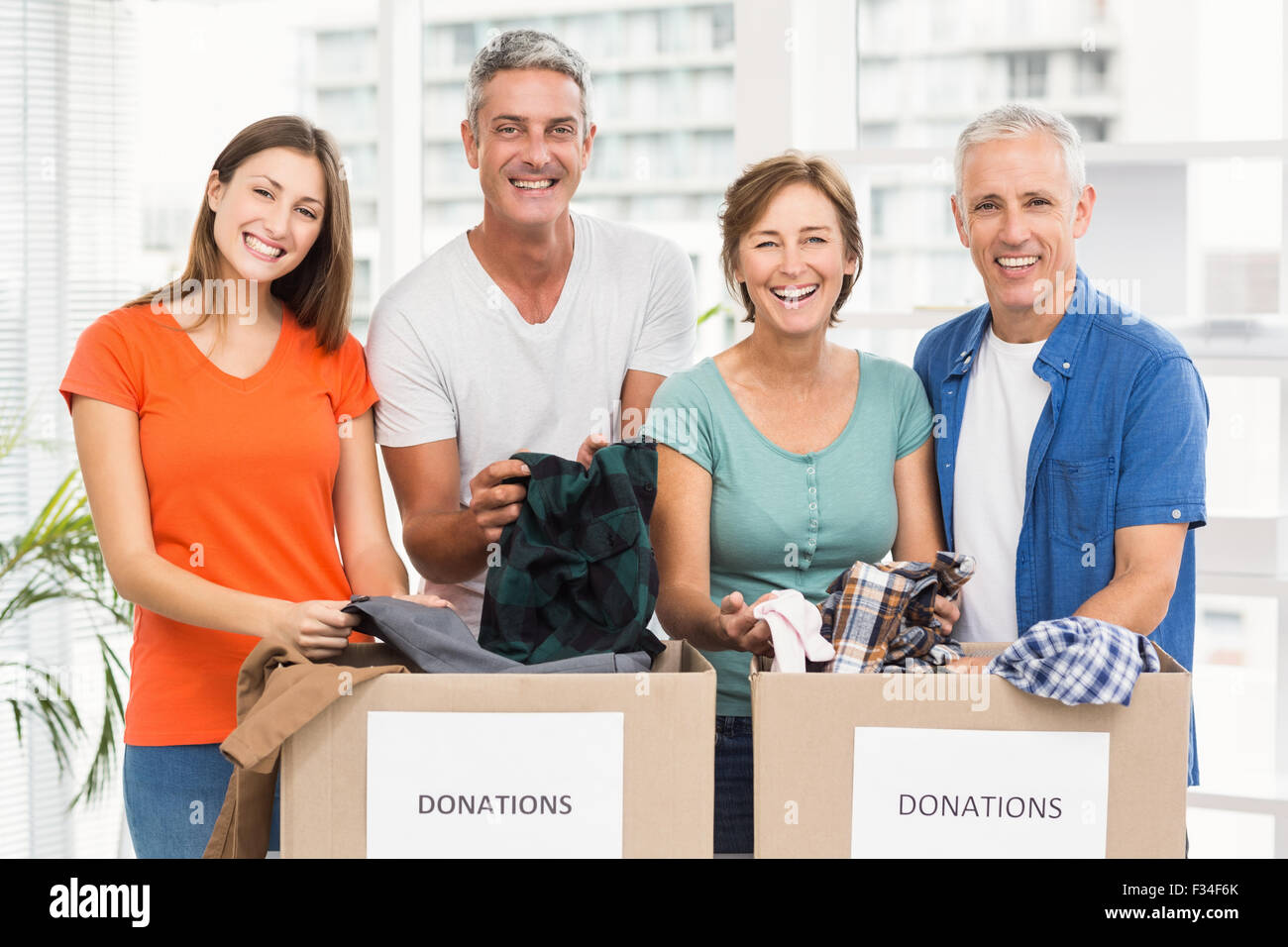 Smiling casual business people sorting donation boxes - Stock Image