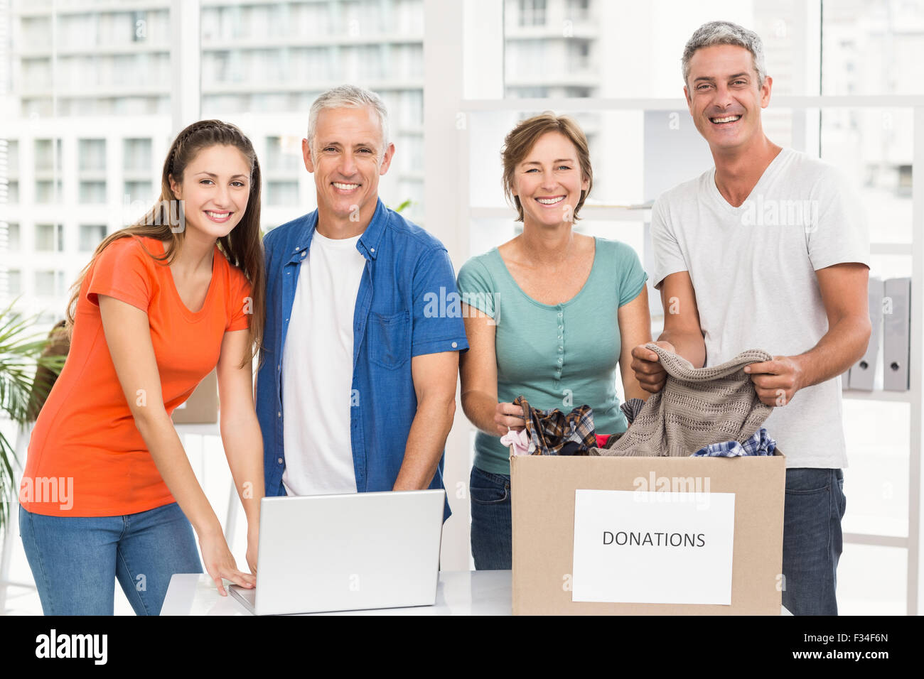 Smiling casual business people with donation box - Stock Image