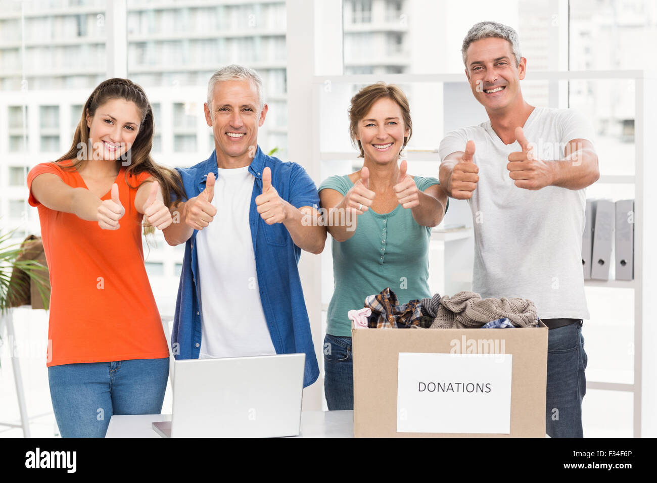 Casual business people donating and doing thumbs up - Stock Image