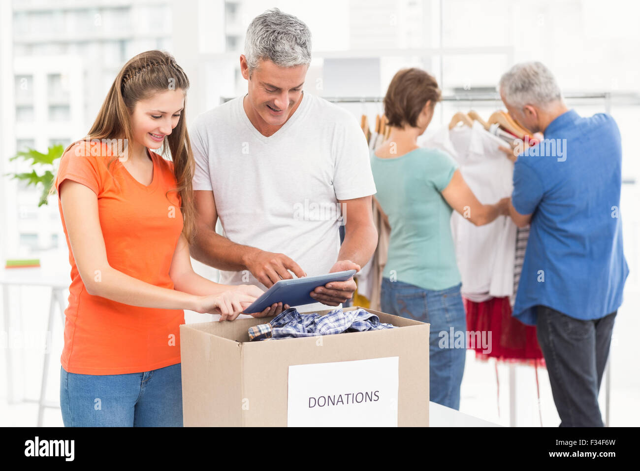 Smiling casual business people sorting donations - Stock Image