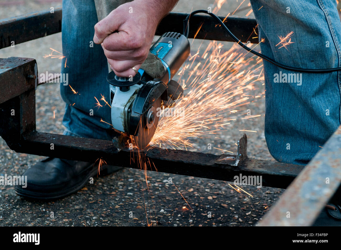 A person angle grinding a boat trailer. - Stock Image