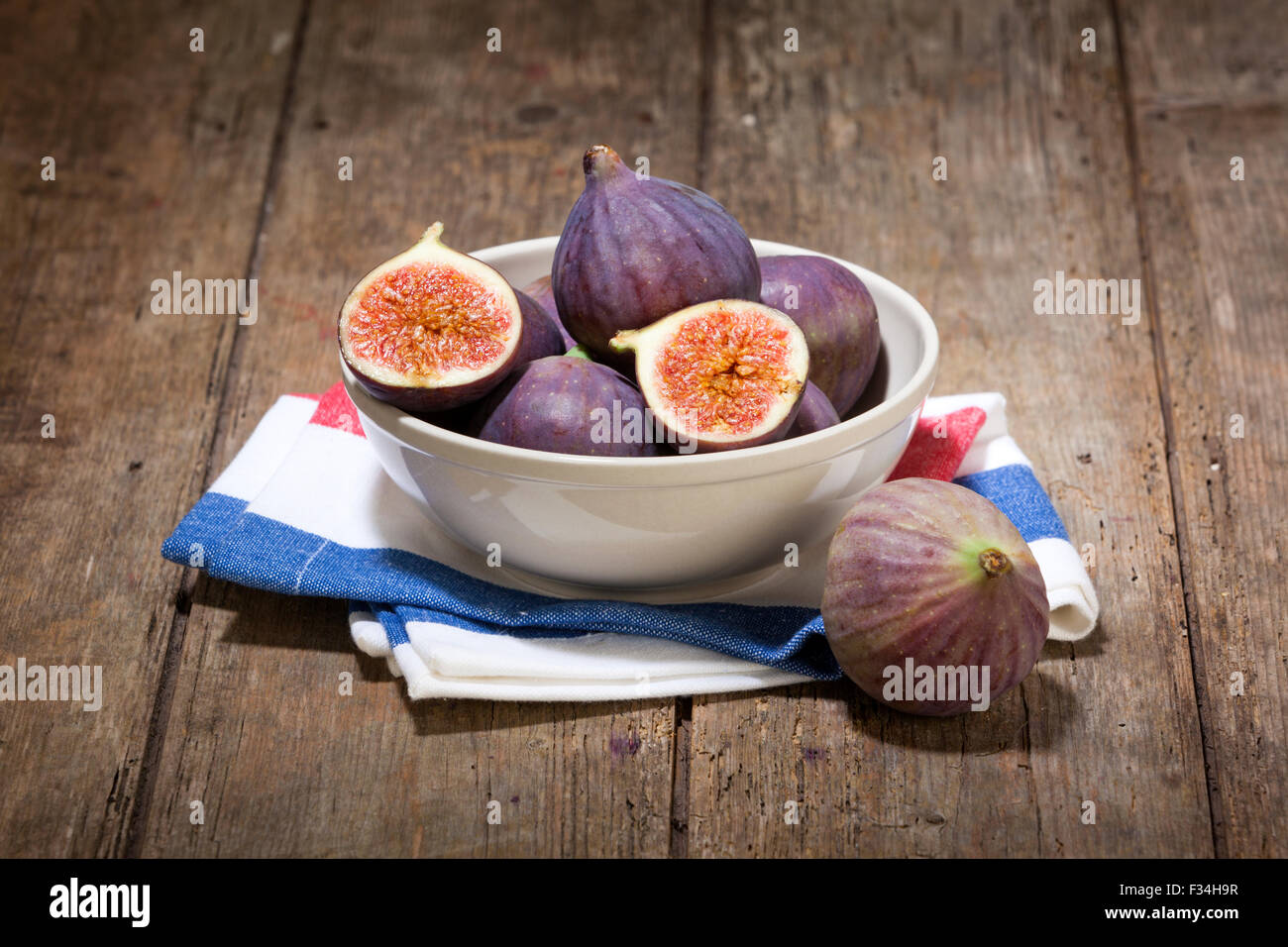 fresh figs in a bowl on dish towel on rustic wooden table - Stock Image