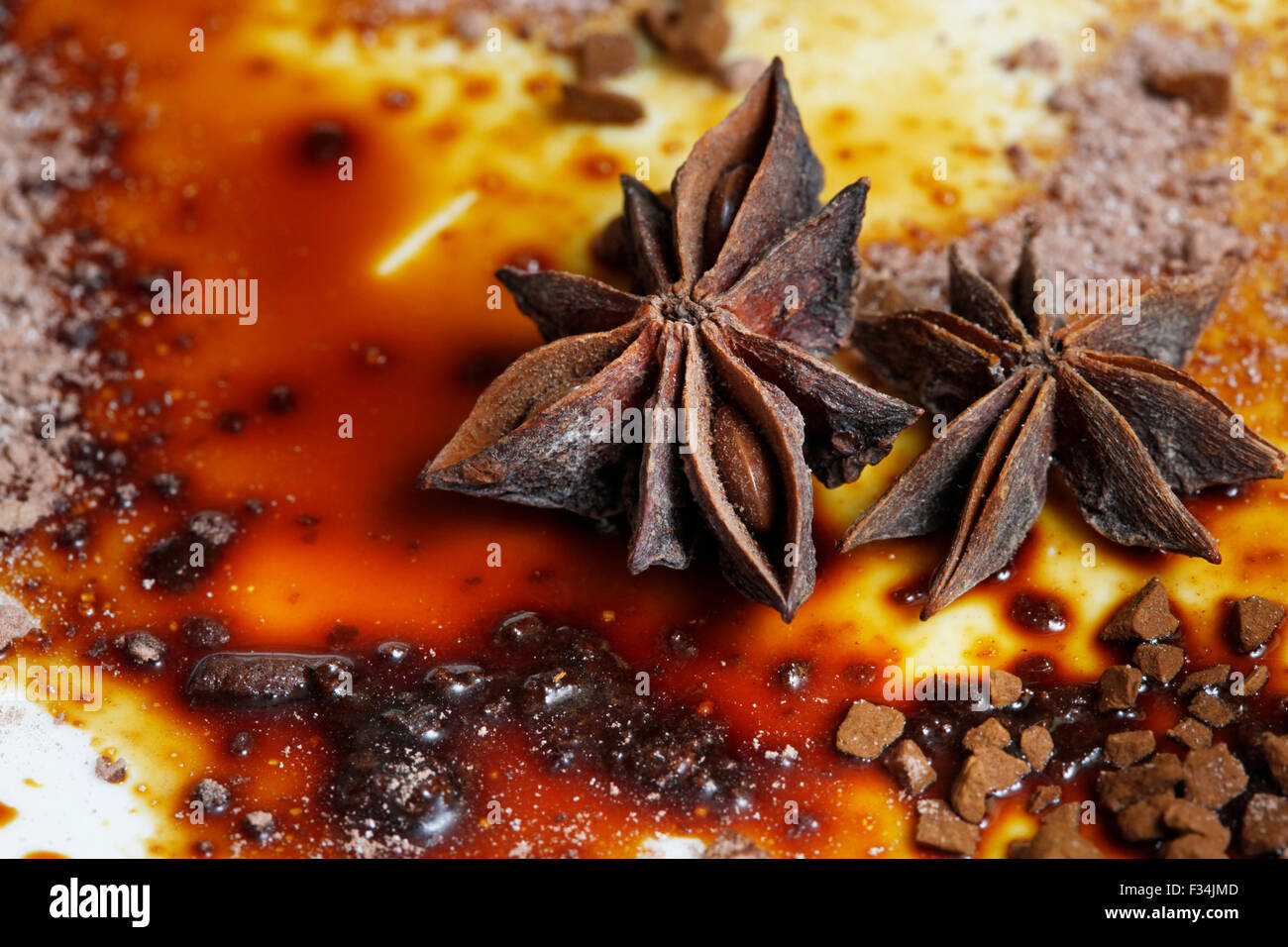 Asterisks anise on a plate with chocolate sauce - Stock Image