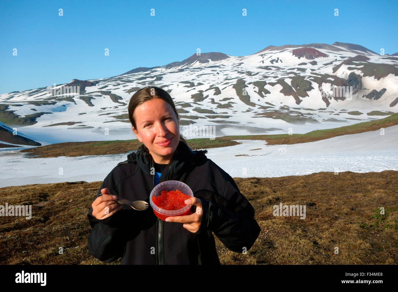 Female tourist eating red caviar with the Gorely volcano on the background, Kamchatka Peninsula, Russia - Stock Image