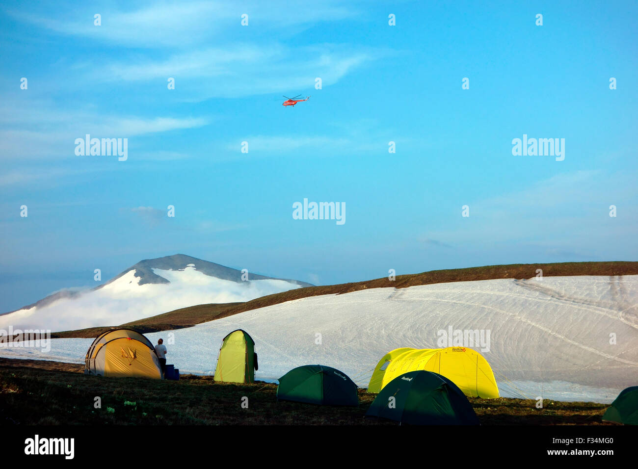 Helicopter flying over the tourists tents, Gorely volcano base camp, Kamchatka Peninsula, Russia - Stock Image