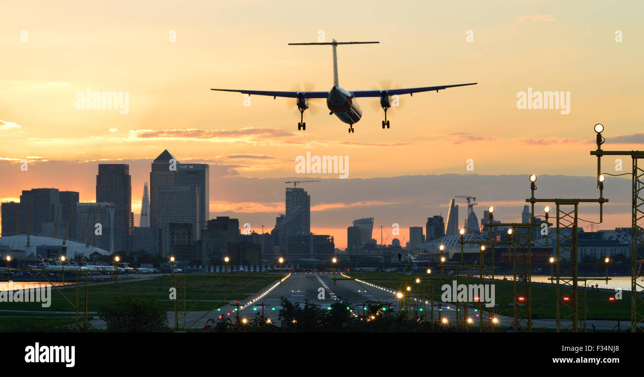FlyBe Dash8 landing at London City Airport at sunset - Stock Image