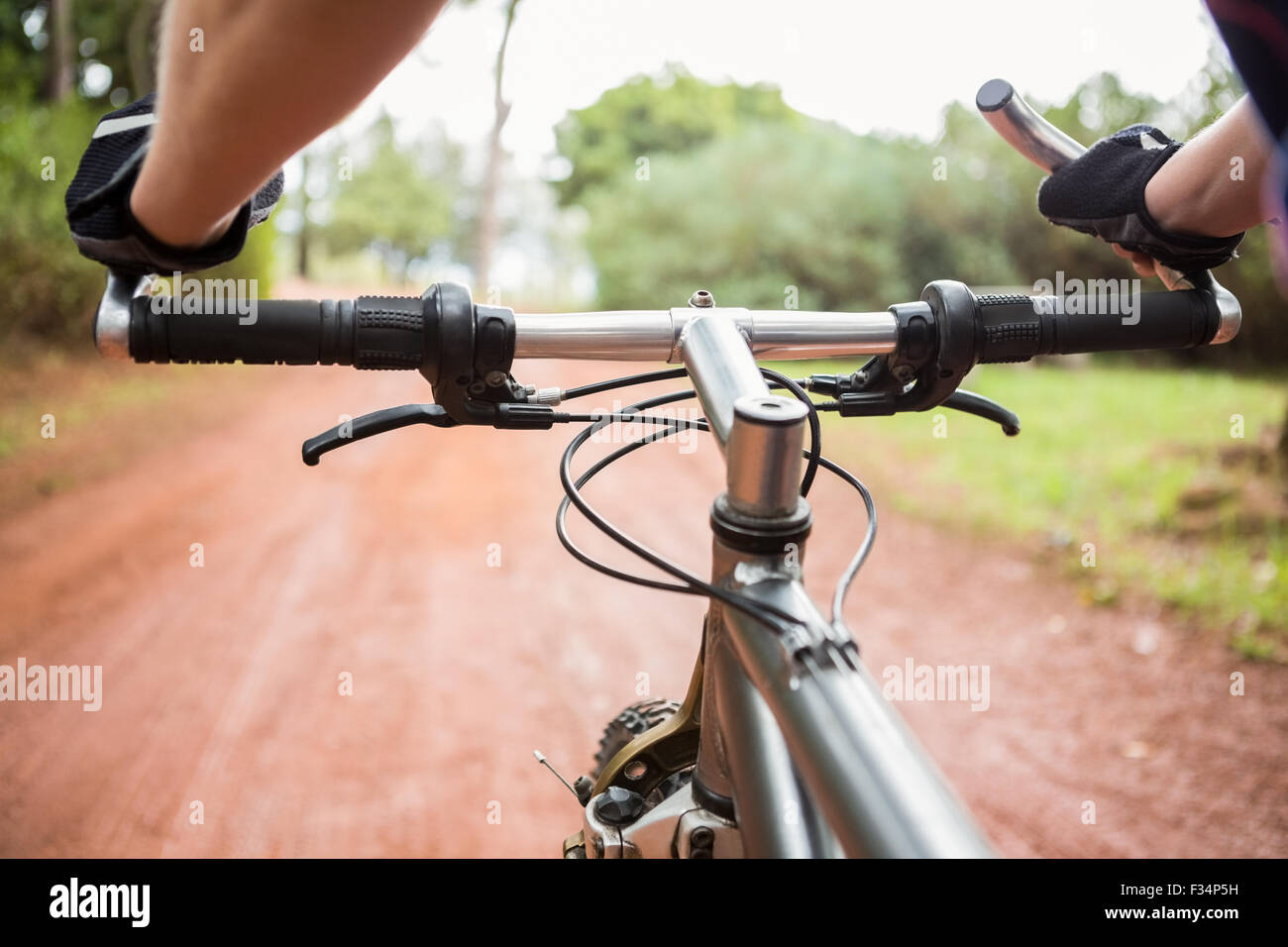 Woman mountain biking and holding handlebars - Stock Image