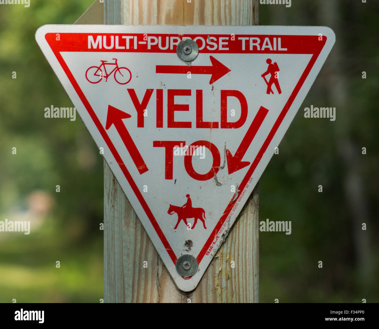 Yield sign at a recreation trail for hiking, biking, horseback riding, and in the winter snowmobiling. - Stock Image