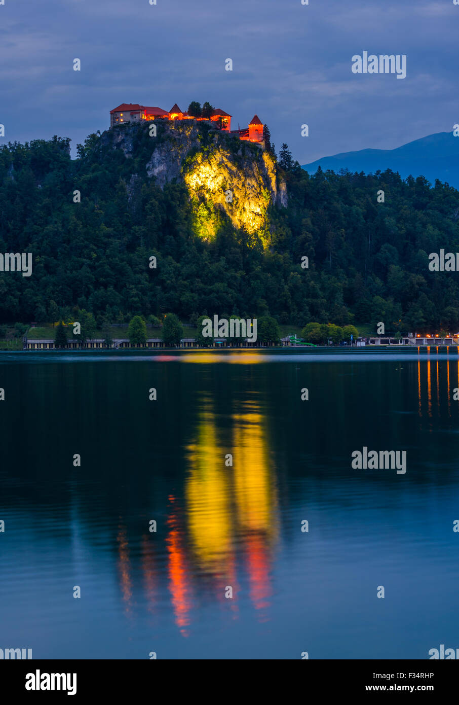 Illuminated Bled Castle at Bled Lake in Slovenia at Night Reflected on Water Surface - Stock Image