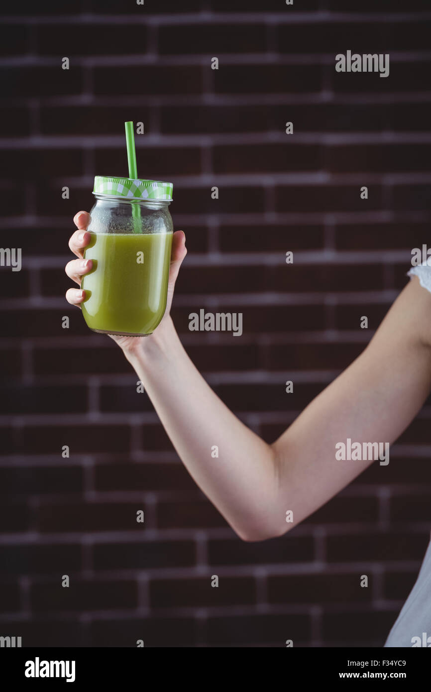 Pretty woman sipping on green juice - Stock Image