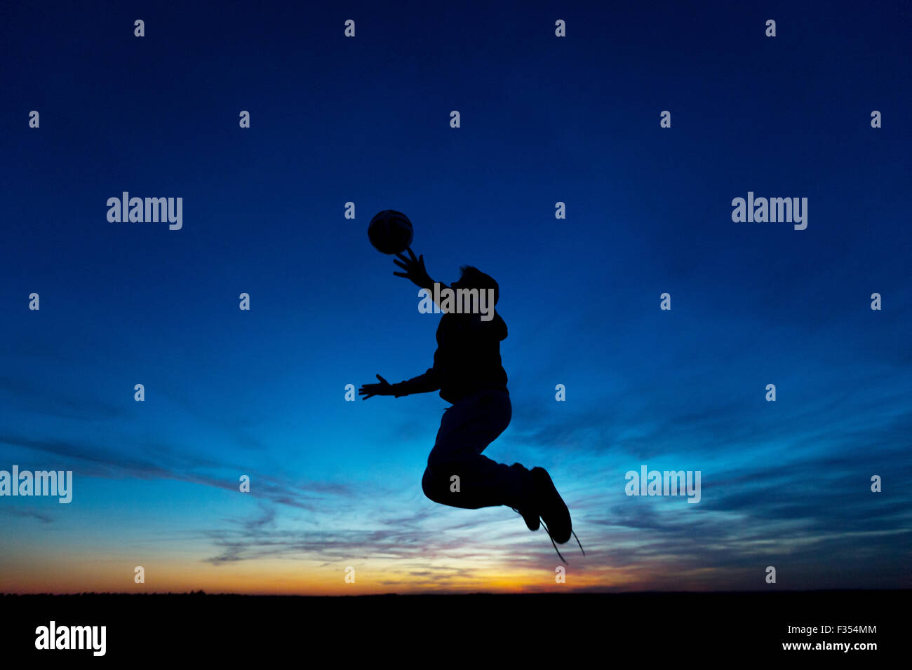 silhouette of a boy playing outside at dusk - Stock Image