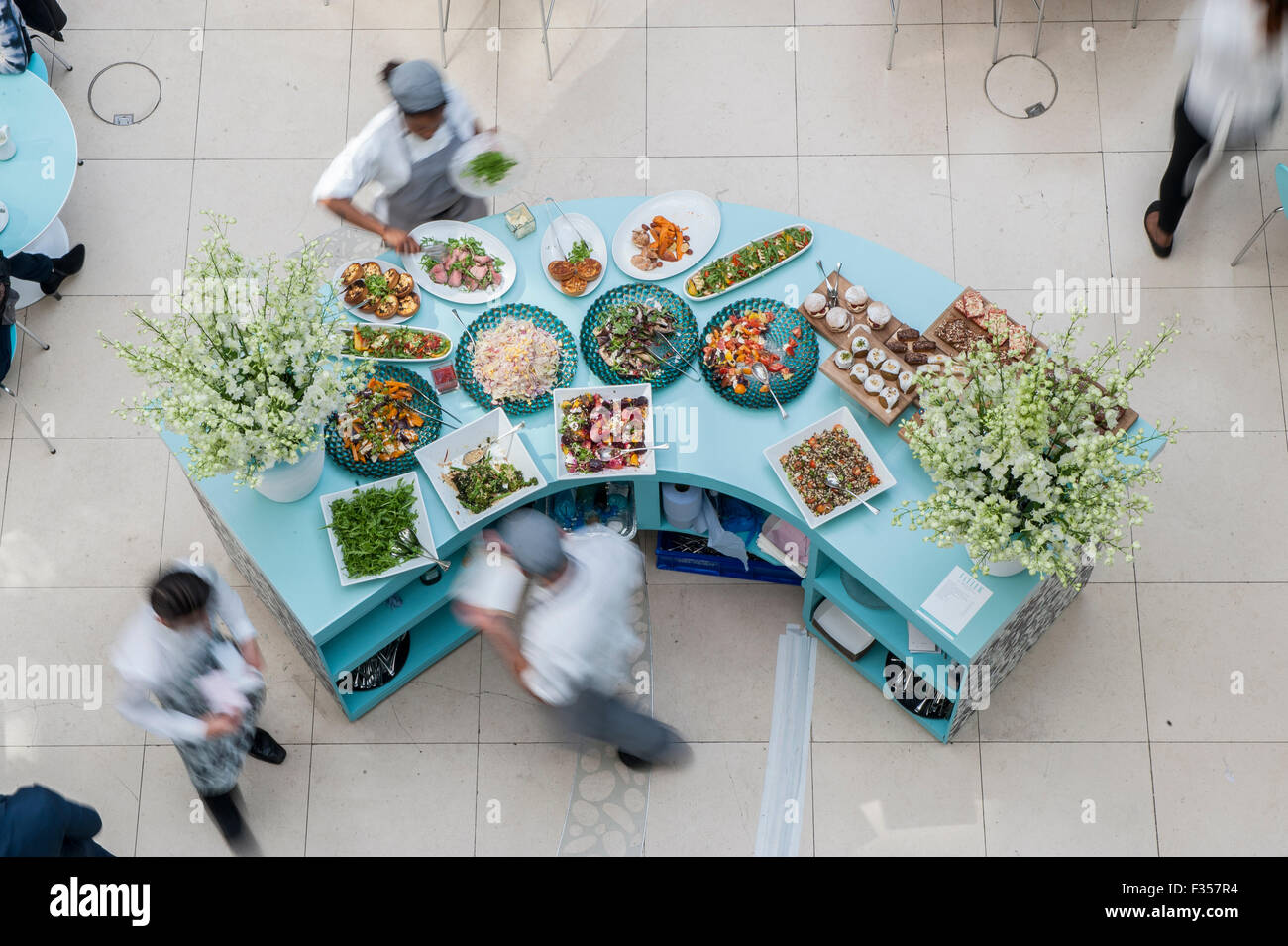 Chefs and waiters race around a food counter - Stock Image