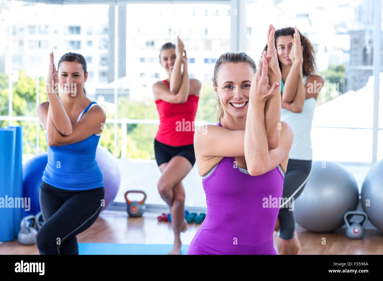 Attractive women doing eagle pose - Stock Image