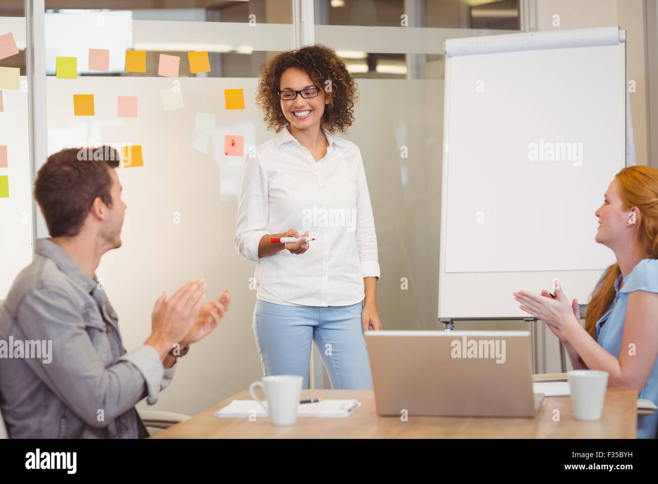 Colleagues appreciating businesswoman in meeting - Stock Image