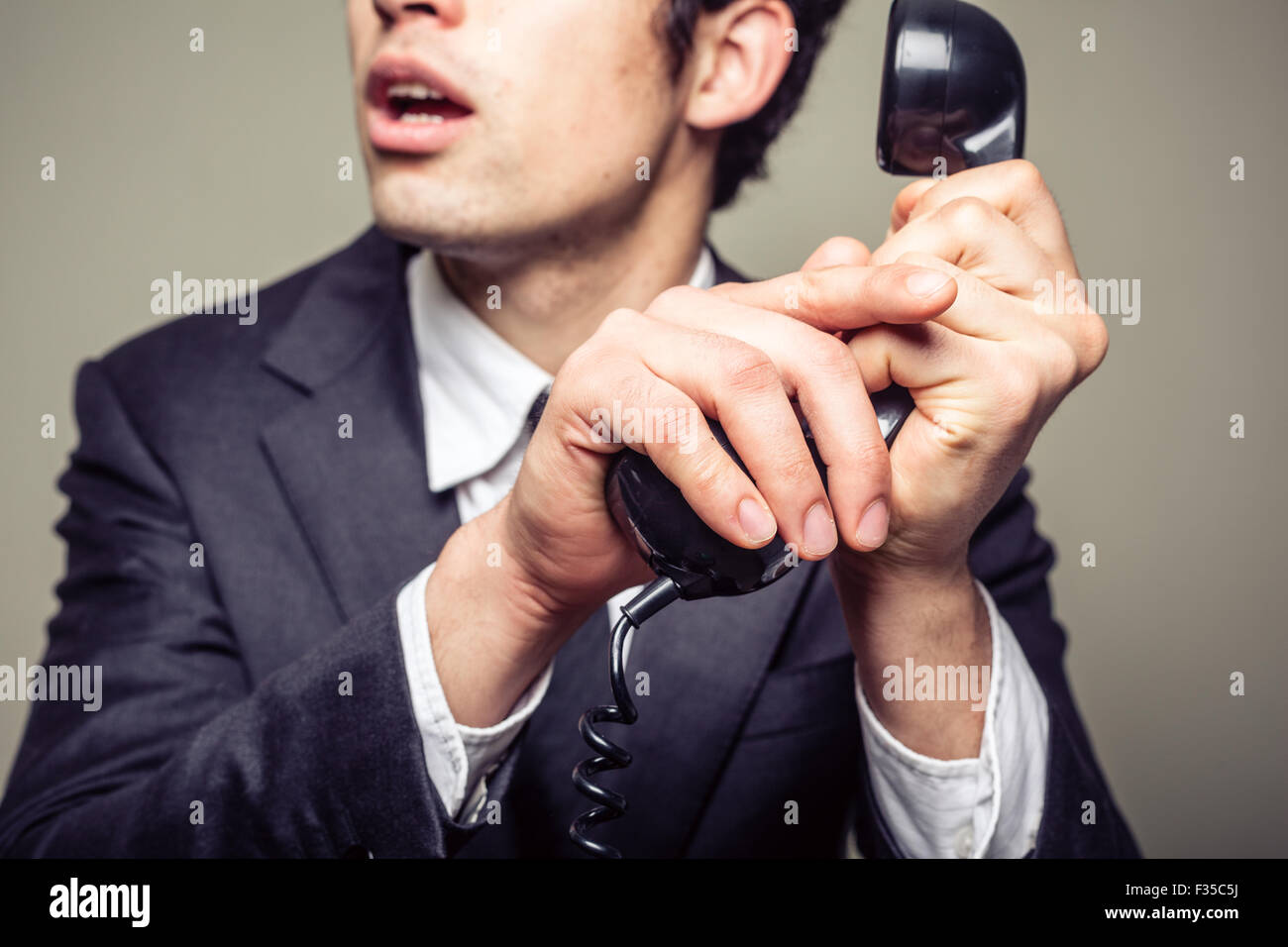Businessman is covering the phone to speak in private to someone in the room - Stock Image