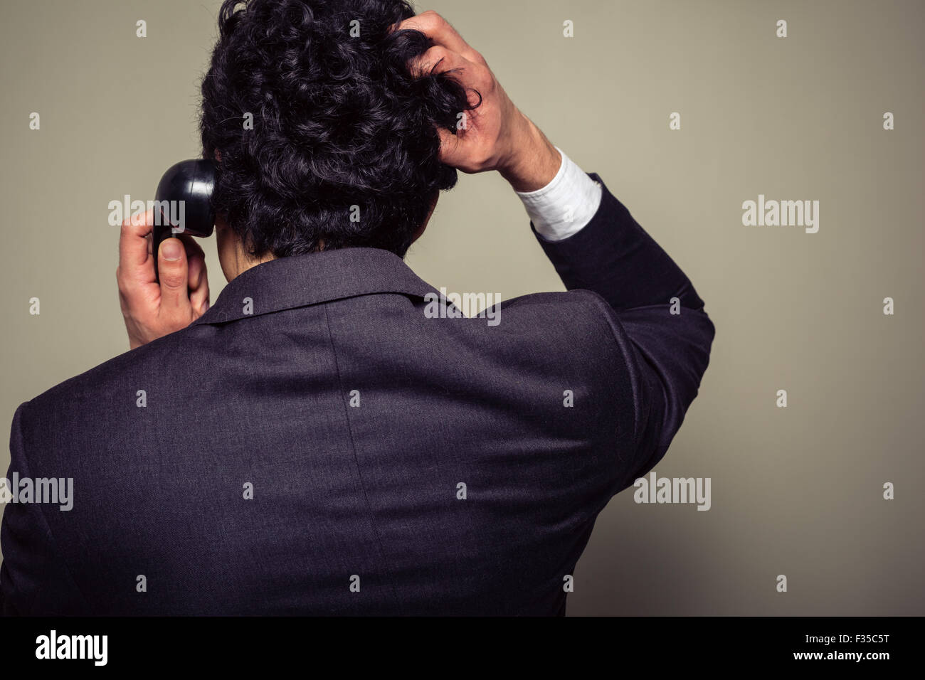 Rear view of a confused businessman on the phone scratching his head - Stock Image