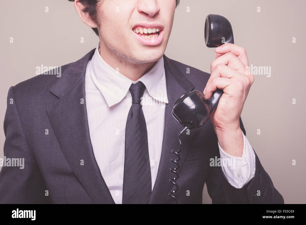 Young businessman can't believe what he is hearing on the phone - Stock Image
