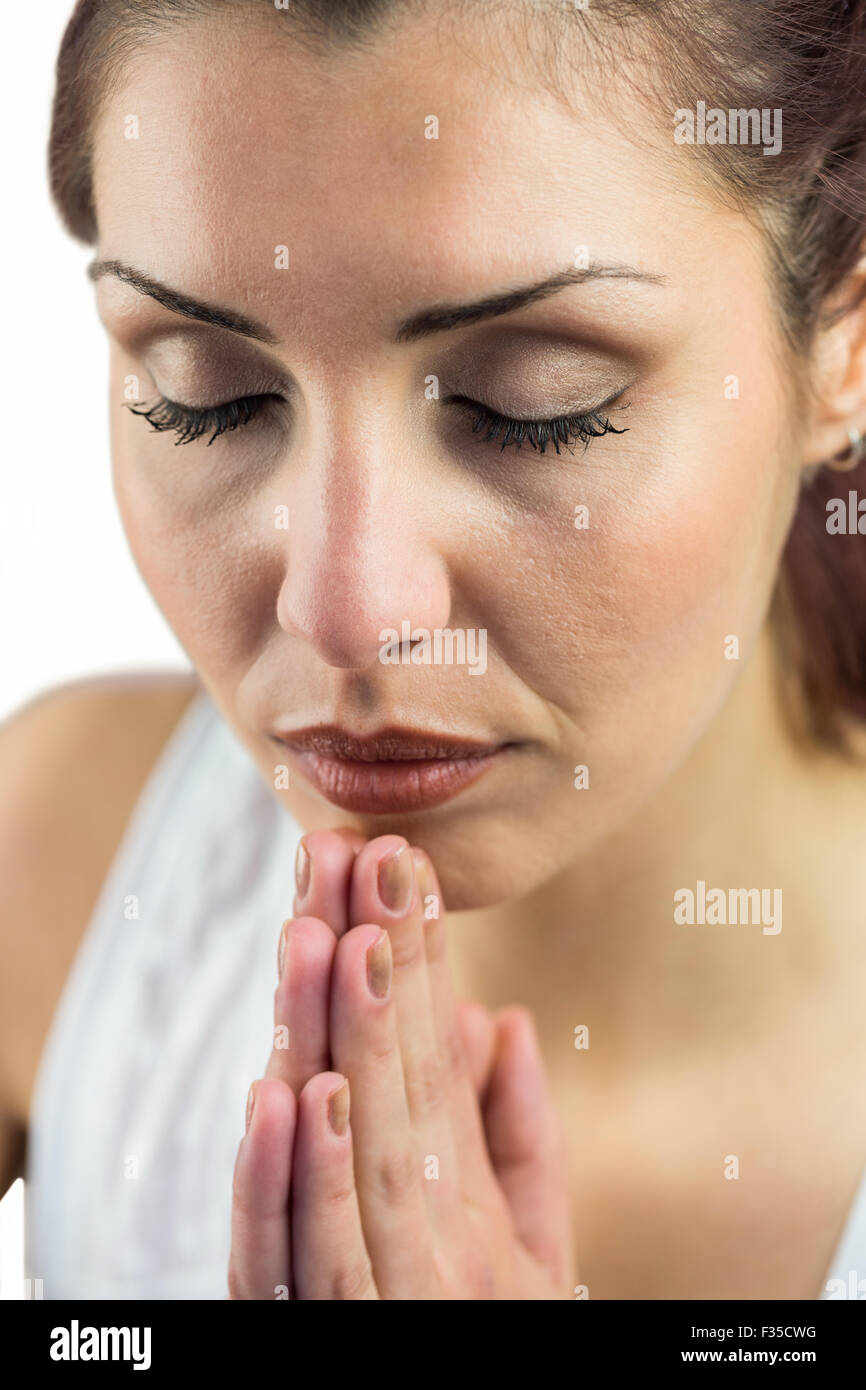 Close-up of woman with eyes closed and joined hands - Stock Image