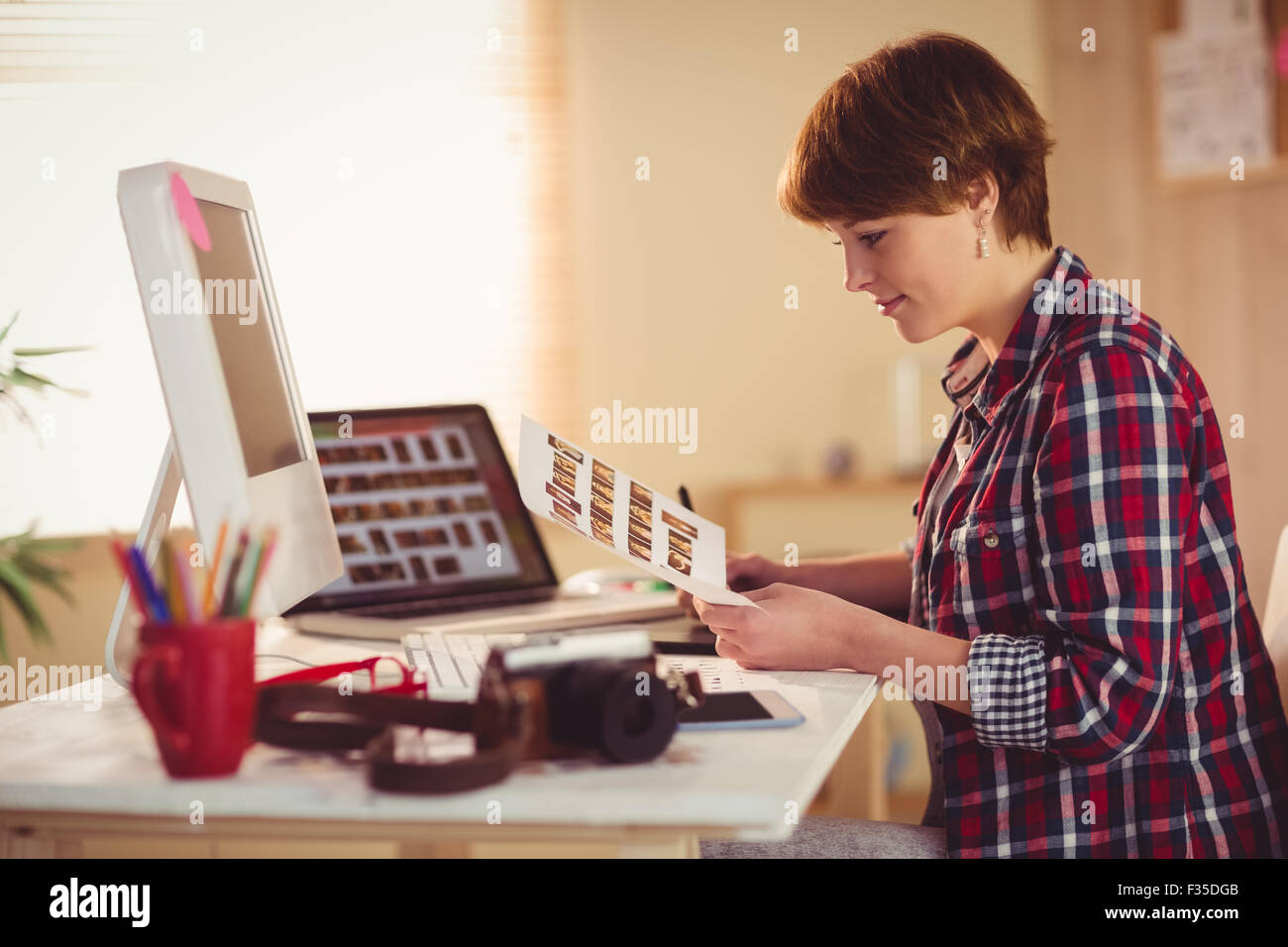 Smiling photographer looking pics at her desk - Stock Image