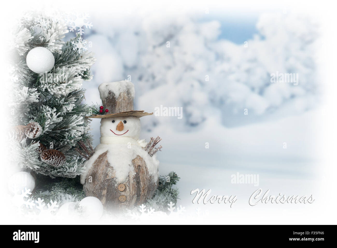 Merry Christmas greeting card with snowman next to tree - Stock Image