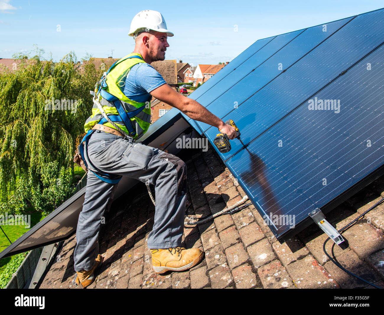 Roofer fitting a domestic solar panel system - Stock Image