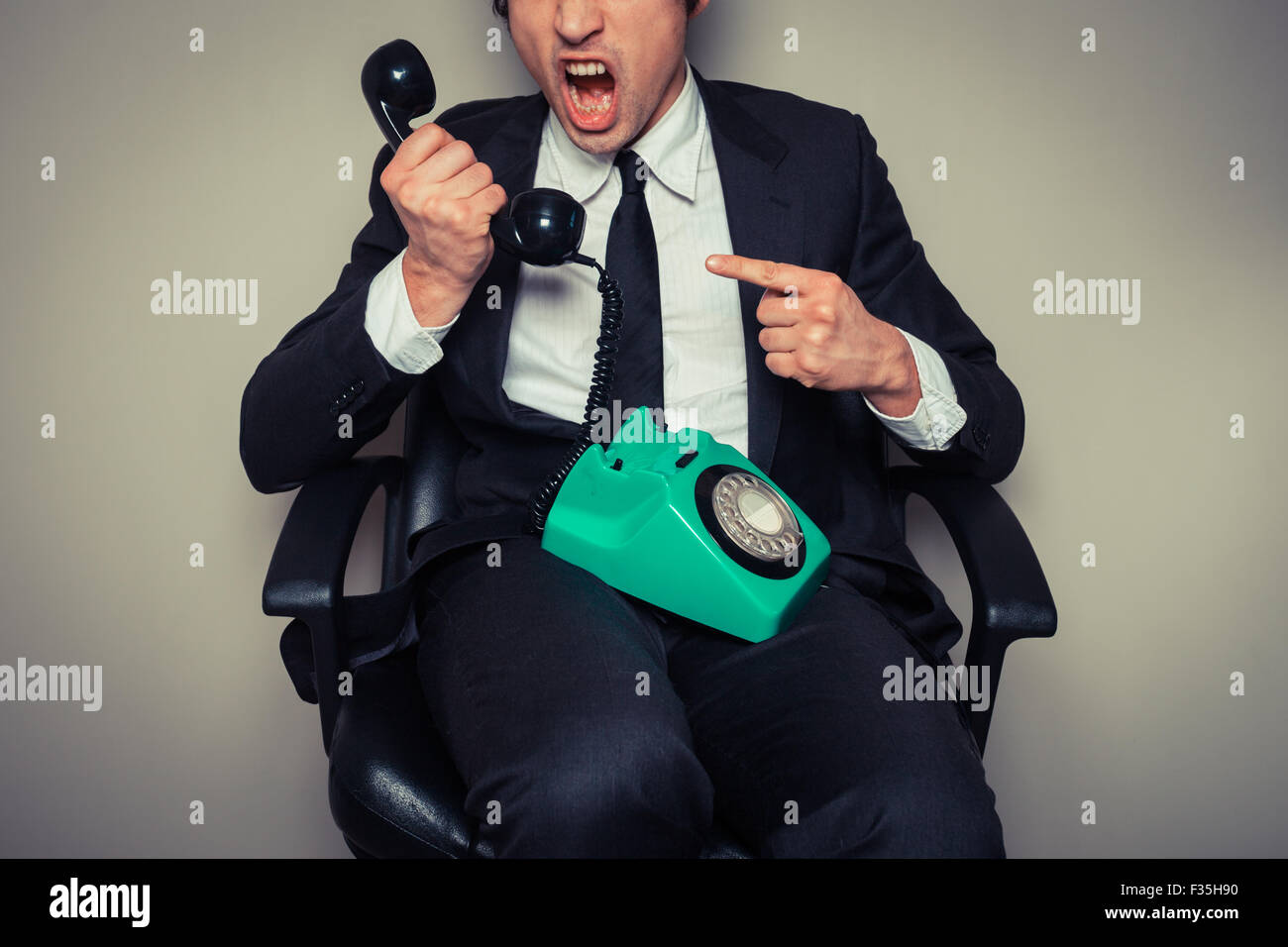 Angry businessman in office chair is on the phone - Stock Image