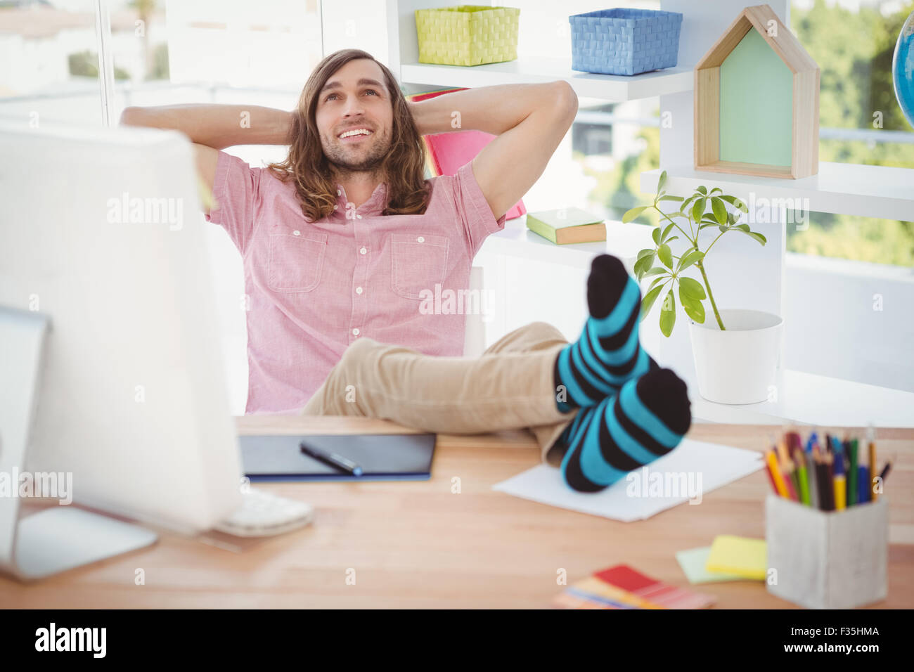 Hipster relaxing with legs on desk - Stock Image