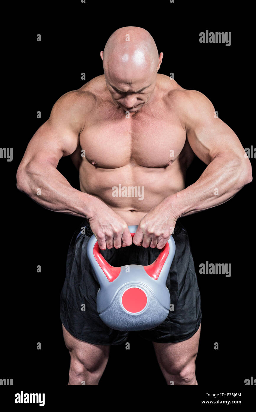 Muscular fit man lifting kettlebell - Stock Image