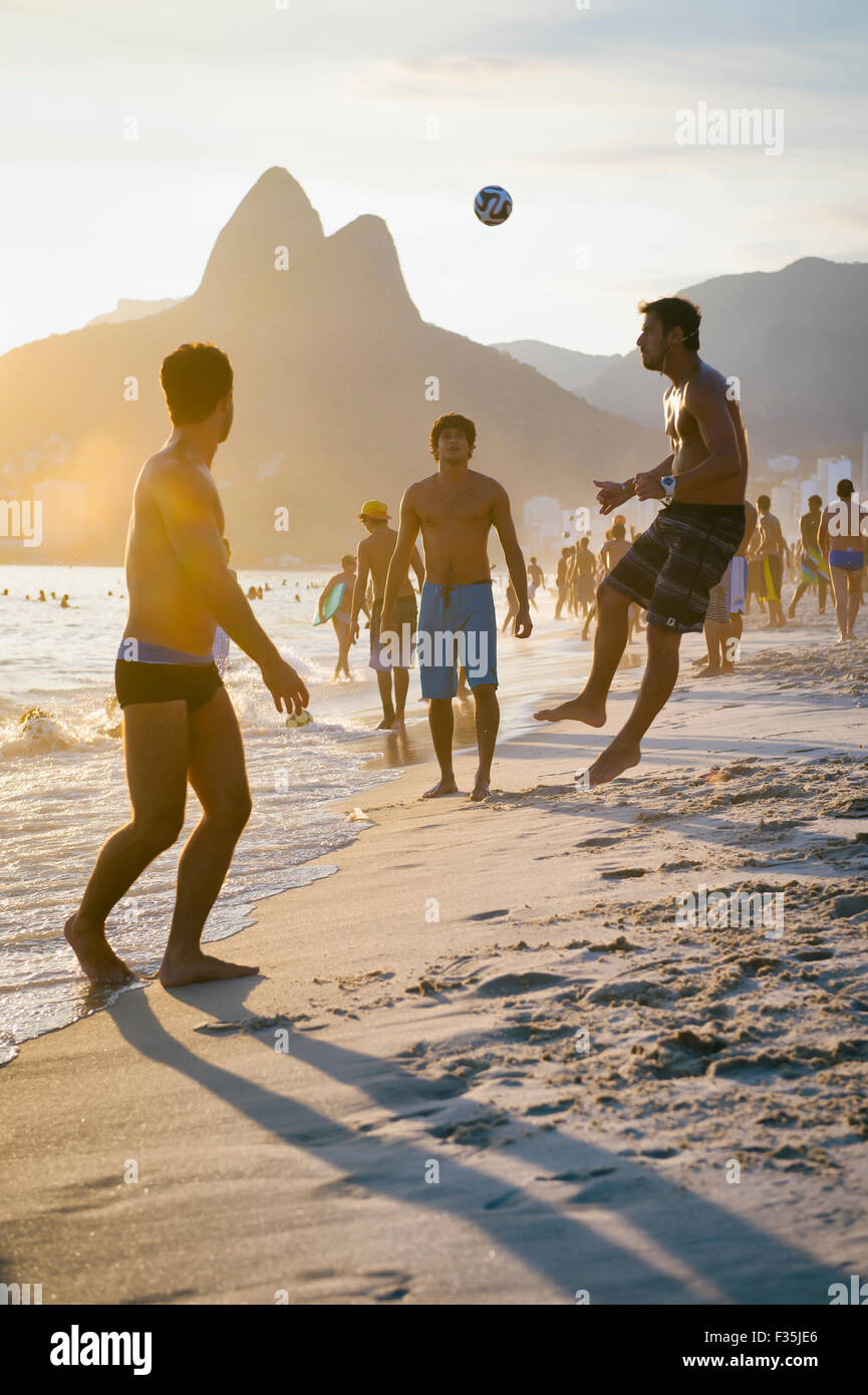 RIO DE JANEIRO, BRAZIL - JANUARY 18, 2014: Young Brazilians play keepy uppy beach football, or altinho, on Ipanema - Stock Image
