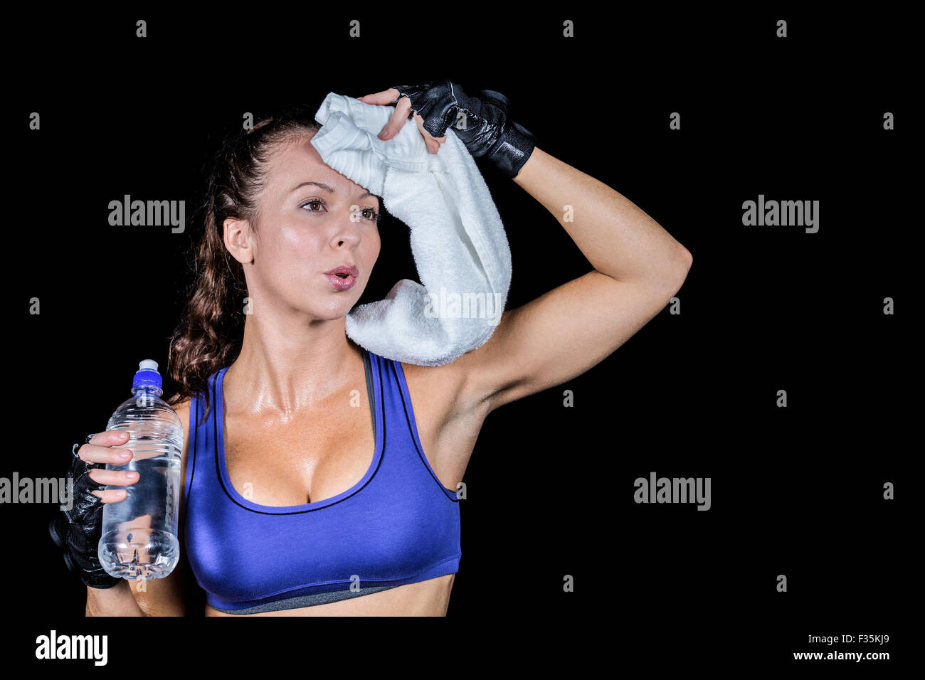 Tired woman wiping sweat while holding water bottle - Stock Image