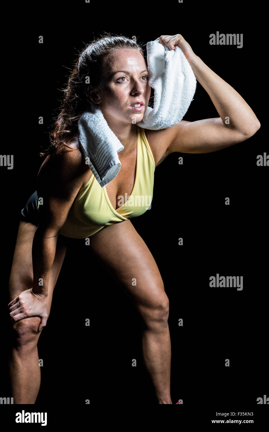 Athlete wiping sweat with towel while looking up - Stock Image