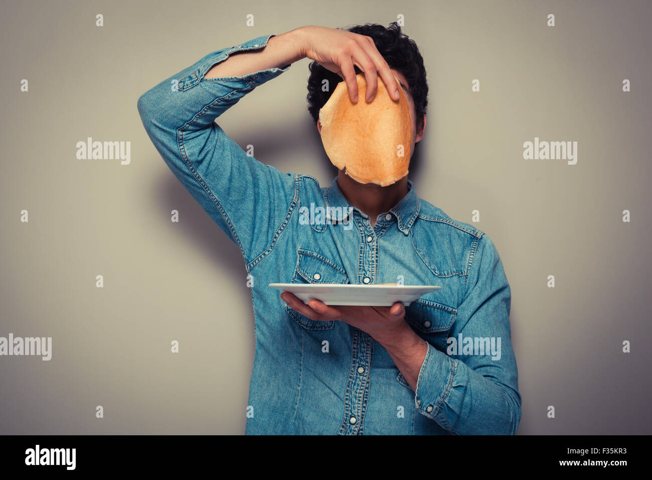 Young man is hiding his face behind a pancake - Stock Image